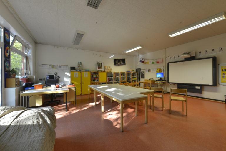Klassenzimmer einer Mittelstufe mit digitalem Whiteboard und Freiarbeitsmaterialien.
