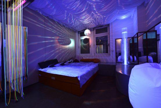 Snoezelraum mit beheizbarem Wasserbett, Diskokugel, schwarzlicht und beleuchteter Wassersäule.